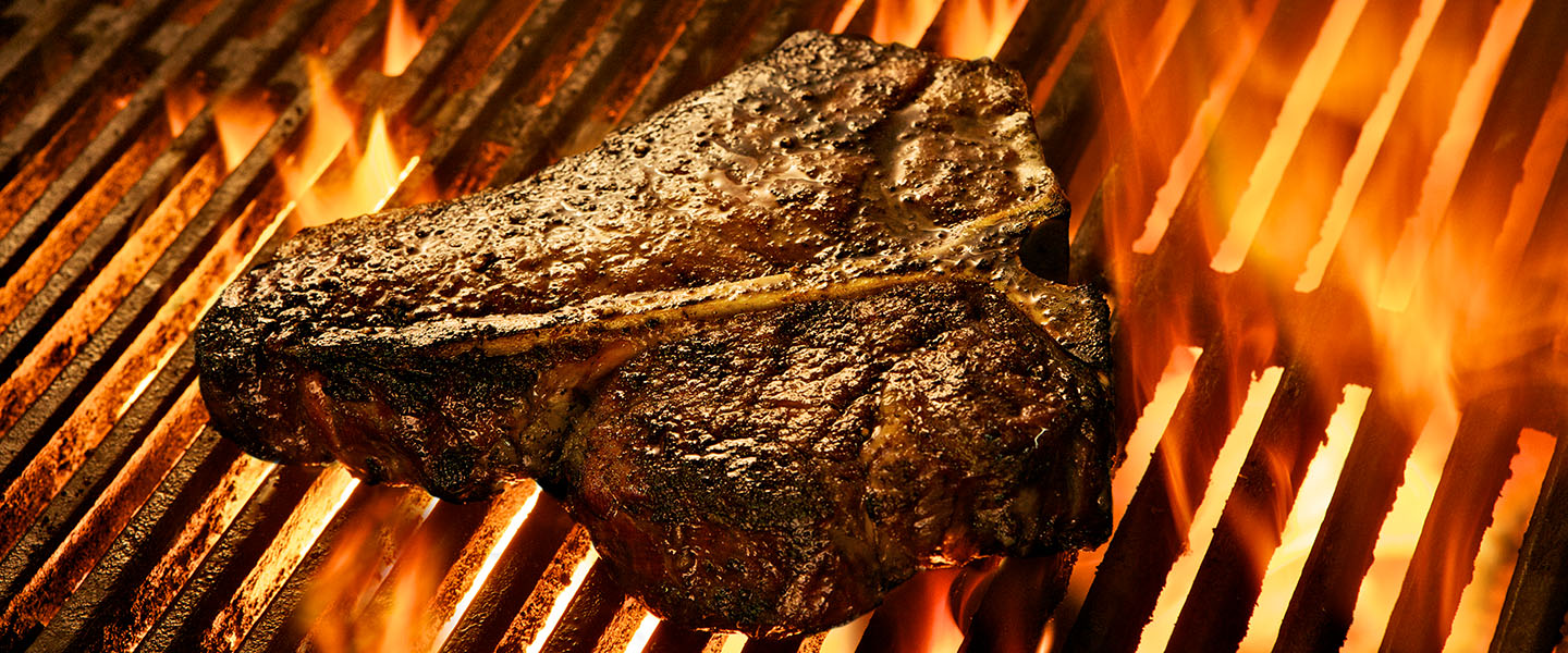 a t-bone steak grilling over charcoal and flames