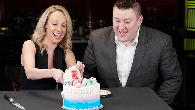 a couple merrily cutting a cake